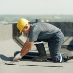A picture of a roofing contractor repairing a flat roof