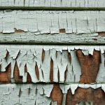 A close-up shot of a wood sided house with fading paint