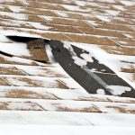 A close-up picture of a missing roof shingle due to ice and snow