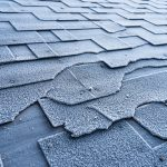 Close up view on Asphalt Roofing Shingles roof damage covered with frost.