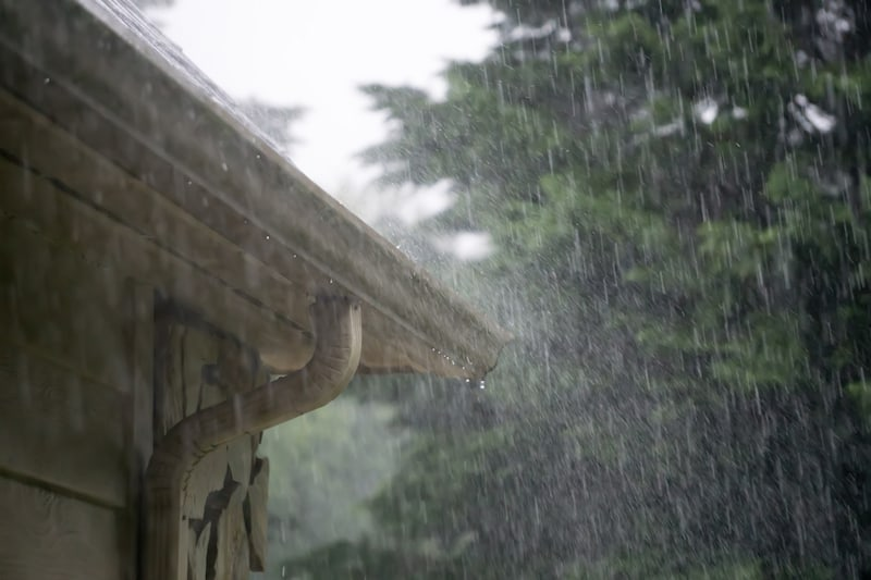 A picture of a roof experiencing a heavy rain downfall